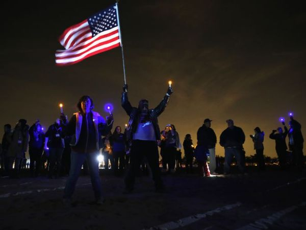 In Midland Beach, Staten Island. A resident raises the flag. Photo Credit: Getty Images