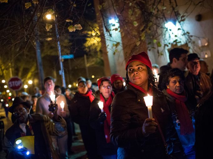 Residents of Red Hook walk together with candles raised. Photo credit: Getty Images