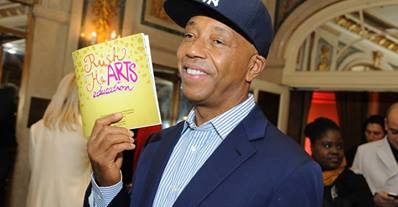 Russell Simmons holding up a program for his HeARTS Valentine's Luncheon. Photo Credit: Facebook