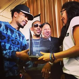 Chance giving out laptops  at the #getconnected event at Chicago's Alcott Prep. Ludacris looks on.